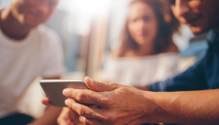 Freunde schauen gemeinsam auf ein Smartphone - neue AY YILDIZ Tarife