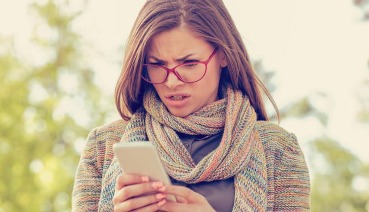 Handy zu langsam: Frau hält Handy in der Hand und schaut verwirrt