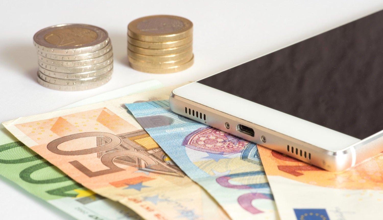 Smartphone mit Geldscheinen und Münzen