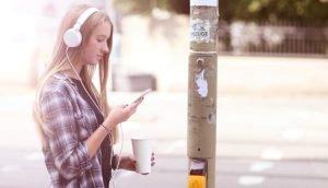 Teenager nutzt Smartphone und Kopfhörer