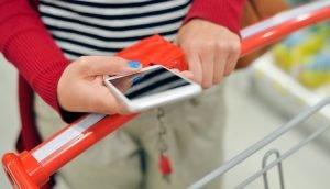 Handybenutzung am Einkaufswagen im Supermarkt
