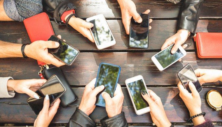 Menschen nutzen Smartphones am Tisch
