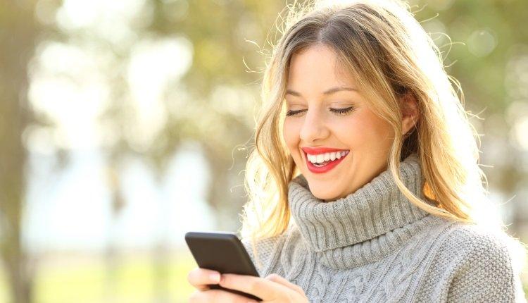 Frau schaut lächelnd aufs Handy