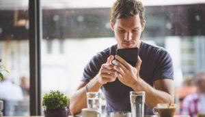 Mann mit Smartphone in Café - Überwachungssystem-app, spy-app