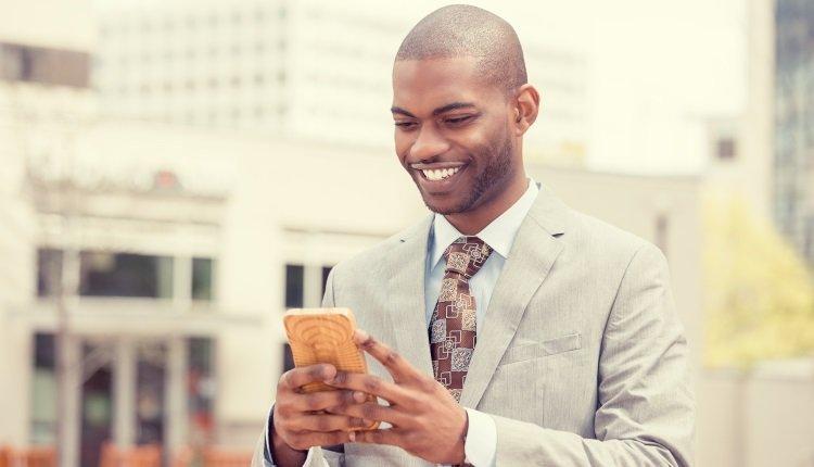 Mann in Anzug schaut aufs Handy