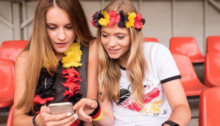 Mädchen schauen im Deutschland-Look auf ihr Smartphone