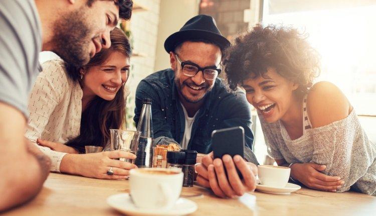 Gruppe sitzt im Café und schaut aufs Handy.