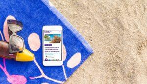 Handy auf einem Strandtuch mit handy.de