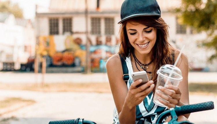 Junge Frau sitzt auf Fahrad und schaut aufs Handy