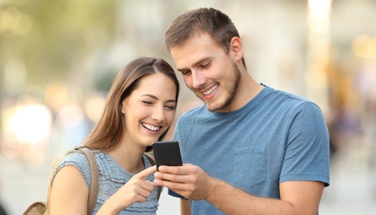 Mann und Frau schauen auf ein Handy