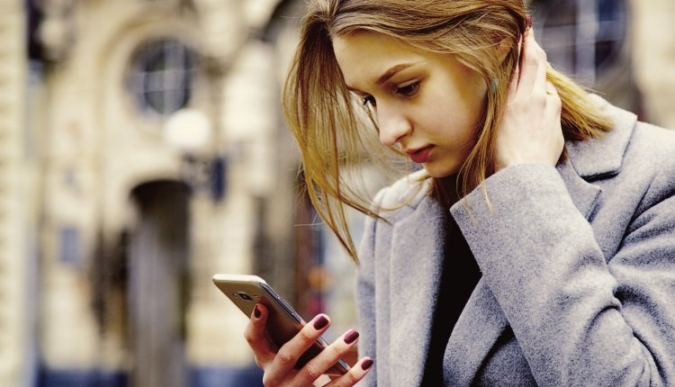 Frau schaut ernst aufs Handy