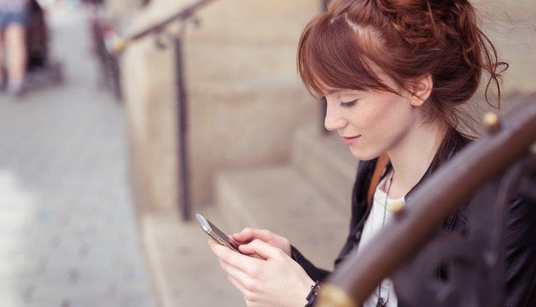 Frau auf der Treppe schaut aufs Handy