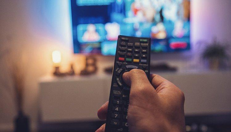 Fernbedienung mit Fernseher im Hintergrund