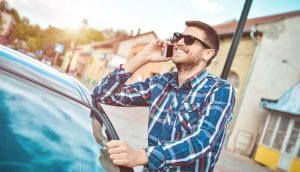 Mann mit Handy am Auto