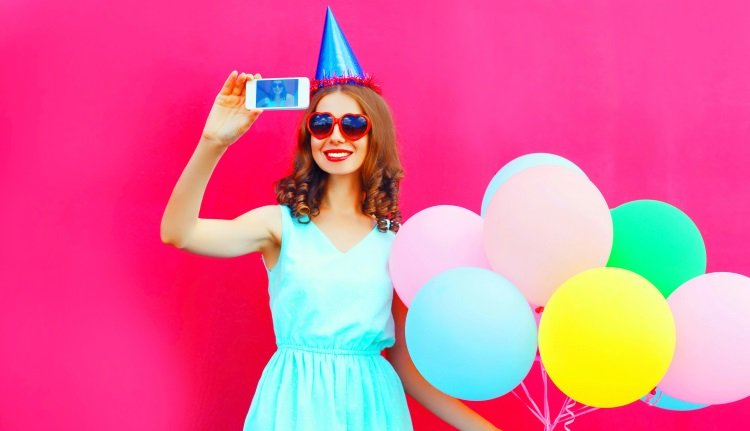 Frau mit Ballons und Handy feiert Geburtstag
