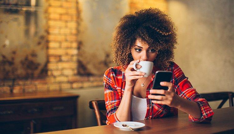 Frau mit Kaffee und Smartphone