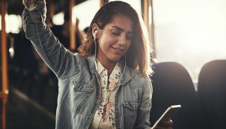 Junge Frau mit In-Ear-Kopfhörer im Bus