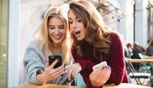 Zwei Frauen schauen auf ihr Handy