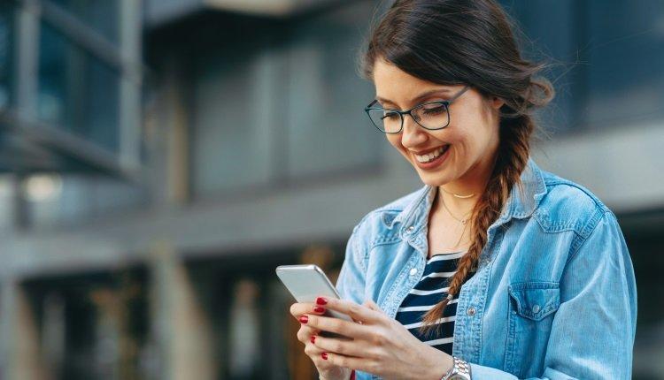 Frau mit Brille schaut aufs Handy