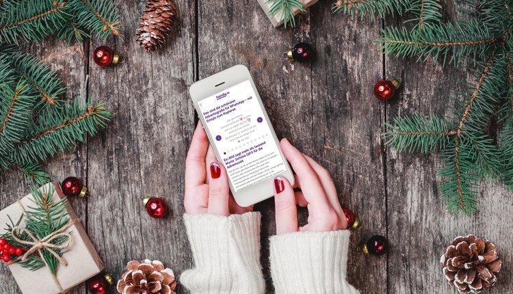 Weihnachtlicher Tisch mit Frau und Smartphone in der Hand mit den schönsten Adventsgrüßen für WhatsApp