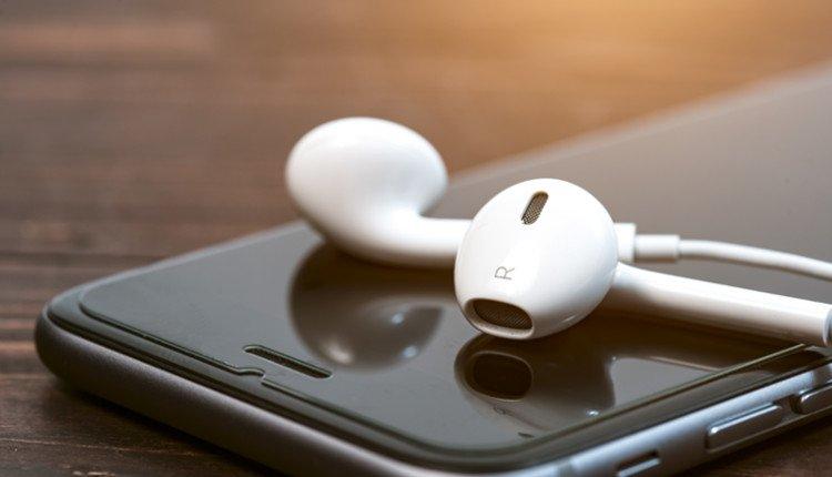Weiße In-Ear-Kopfhörer liegend auf iPhone-Display