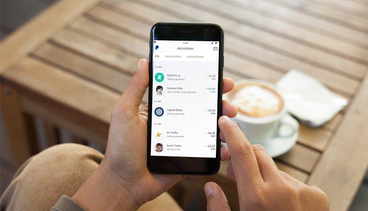 PayPal-App auf einem Smartphone in der Hand eines Mannes - Achtung, Virus!