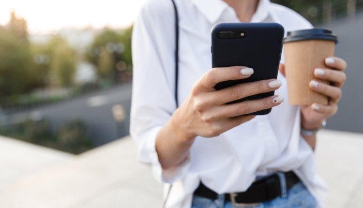 Frau trägt Handy und Coffee-to-Go