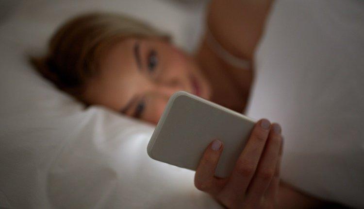 Smartphone im Schlafzimmer Frau