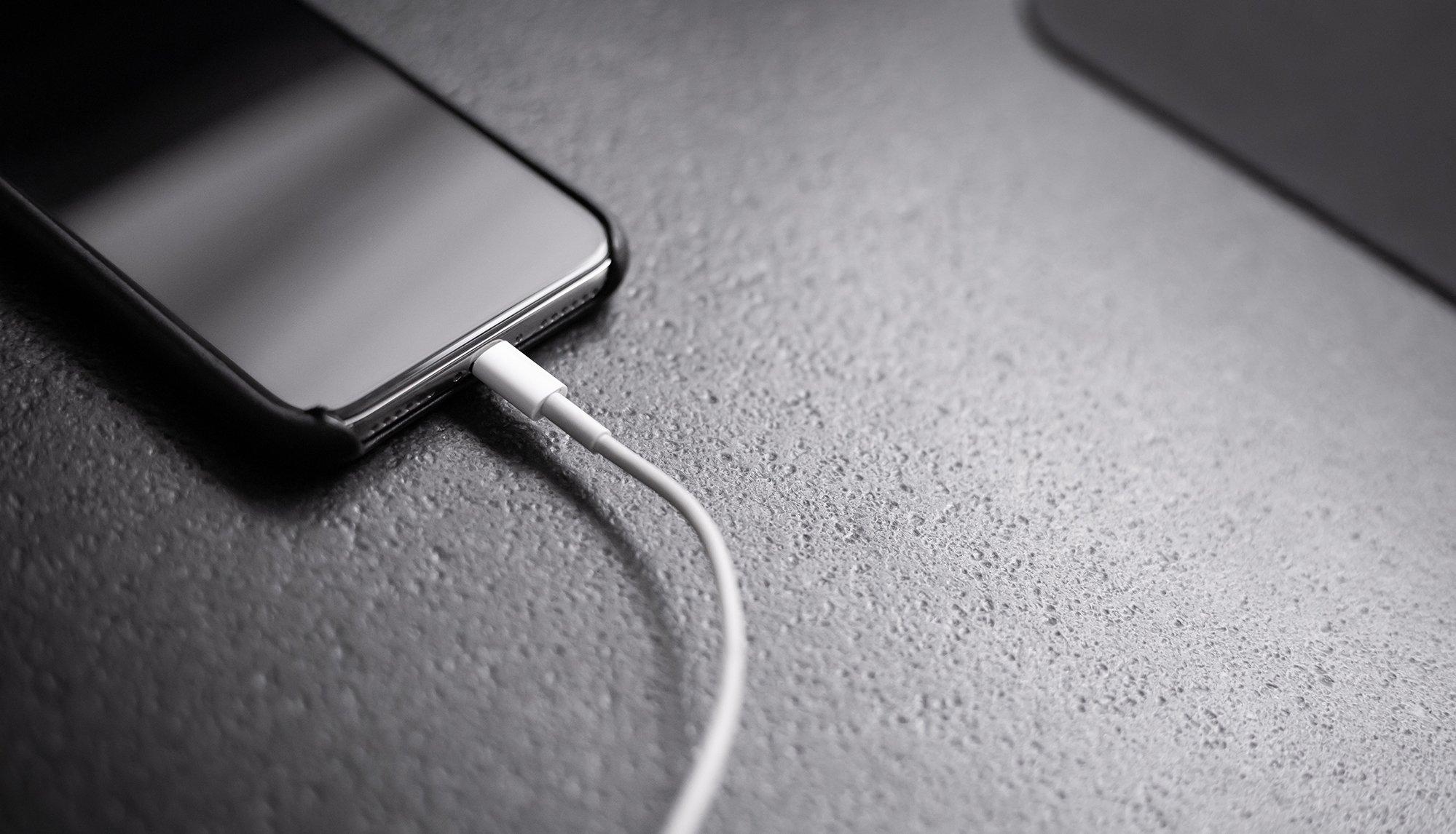 Ein iPhone wird mit Lighning-Kabel geladen. Akku ist leer.
