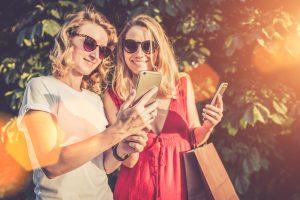 Ein Sommertag, zwei Frauen stehen lächelnd im Park und schauen sich Fotos auf dem Smartphone des anderen an. Die Frauen machen eine Pause nach einer ausgiebigen Shopping Tour