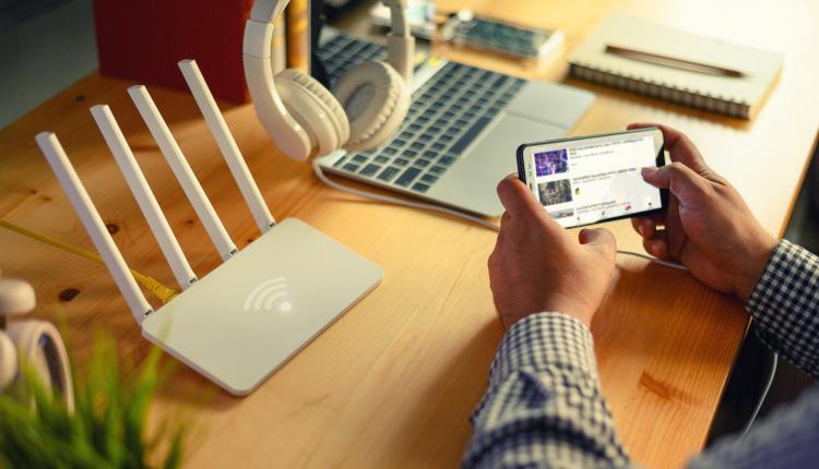 Nahaufnahme eines WLAN Routers und einem Mann der ein Smartphone nutzt und dabei am Tisch sitzt zuhause